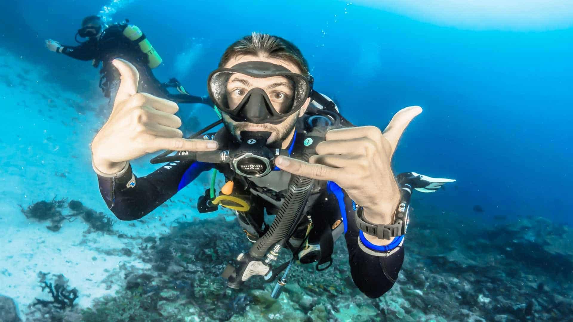Happy scuba diver making surfer hand signals underwater.